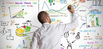 Image of man drawing on a whiteboard that is filled with charts, graphs and illustrations