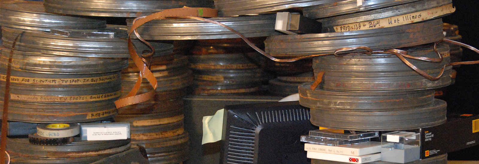 Photograph of old film canisters stacked on desk